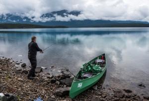 Pappa som fisker i Atlin lake i Canada